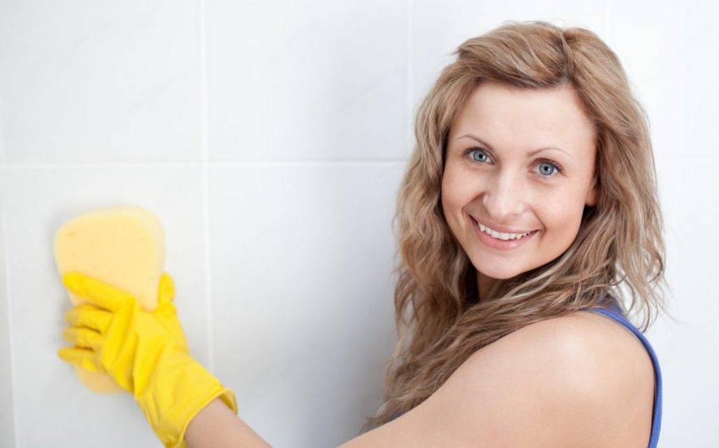 Женщина моет кафель