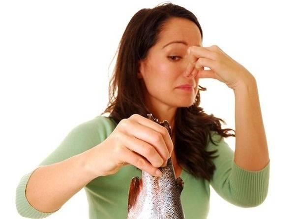 Женщина держит рыбу в руках